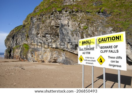 beware of land falls warning sign beside the cliffs in Ballybunion county Kerry Ireland in English and Gaelic - stock photo