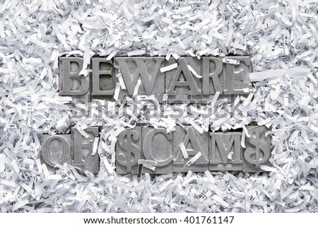 beware of scams phrase made from metallic letterpress type inside of shredded paper heap