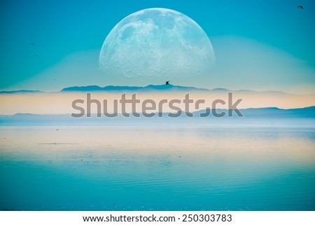 Beyond the Horizon. Fantasy Landscape with Large Moon on the Horizontal, Mountains and the Calm Sea. - stock photo