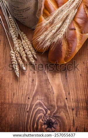 bguettes and wheat ears on vintage wooden board with copyspace food and drink concept  - stock photo