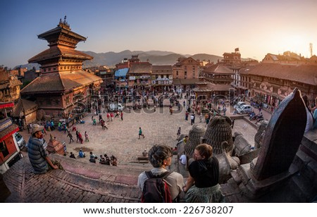 BHAKTAPUR, KATHMANDU VALLEY, NEPAL - APRIL 8, 2014: People preparing for celebration of new year with wooden chariot near Nepalese temples in shape of pagoda at Taumadhi Tole  - stock photo