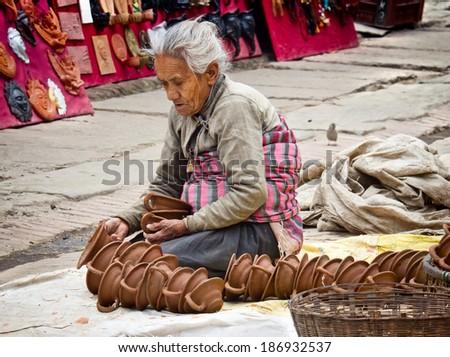 BHAKTAPUR, NEPAL - APR 5: Unidentified Nepalese woman working at the  pottery market, Apr 5, 2014 in Bhaktapur, Nepal.   - stock photo