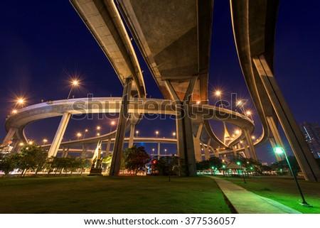"Bhumibol Bridge above park at dawn in Bangkok, Thailand. Foreign text on the bridge is the bridge name ""Bhumibol 1"" - stock photo"