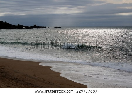 "BIARRITZ, FRANCE- AUGUST 28, 2014  : The Grande Plage, a cool wave and a rocky coast with a view on the ""Rocher de la vierge"" in background. - stock photo"