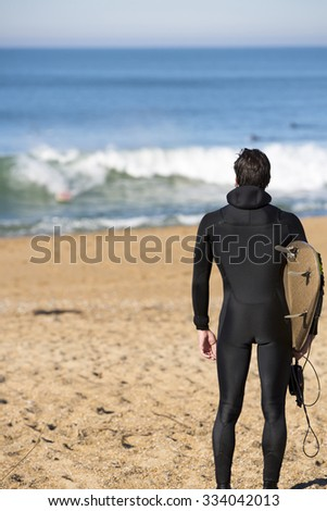 BIARRITZ, FRANCE, DEC 3: Rear view of young surfer man standing on a beach and carrying his surfing board while looking at the Atlantic Ocean during a sunny day in Biarritz. France 2013 - stock photo