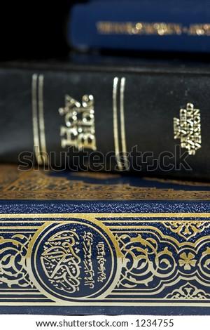 Bible and Koran (Qur'an) and Book of Mormon (focus on Koran) - stock photo