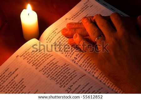 Bible by candle light with hands resting on it - stock photo