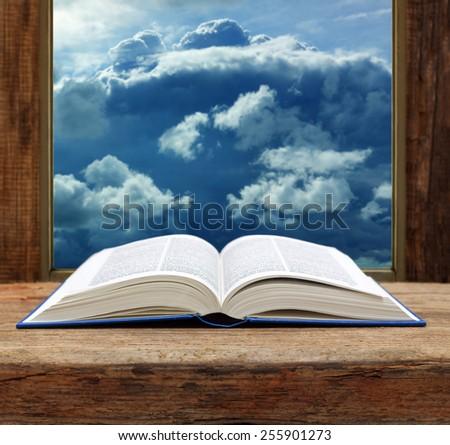 Bible open book  wooden window sky view stormy cloud - stock photo