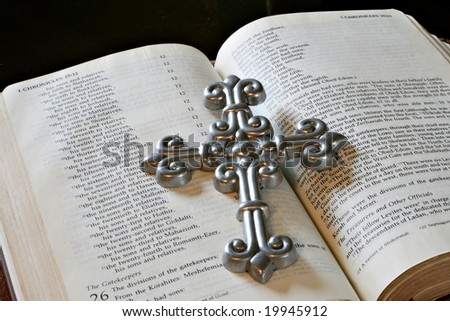 Bible open pages with silver cross - stock photo