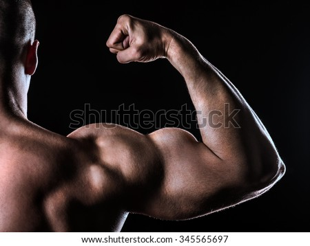 bicep of bodybuilder from behind on black background - stock photo
