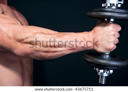 Bicep with hand weight close up , isolated on black background - stock photo