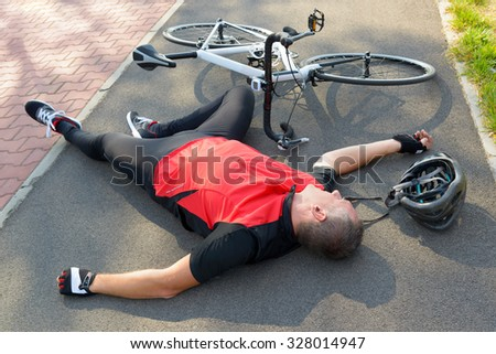 Bicycle accident. Biker lying on the road - stock photo