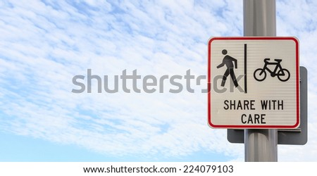 Bicycle and pedestrian shared route sign on pole post against blue sky background, concept of share with care. (Left space for text) - stock photo