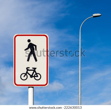 Bicycle and pedestrian shared route sign on pole post against the blue sky background. - stock photo