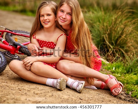 Bicycle children. Happy sisters rides bicycle. Children have rest on country road in park. Bicycle children posing on camera near bicycle into park. - stock photo