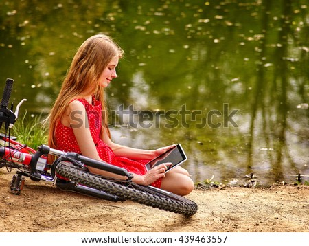 Bicycle girl. Girl wearing red polka dots dress recreation near bicycle into park and watch tablet pc. Girl sits near water. - stock photo