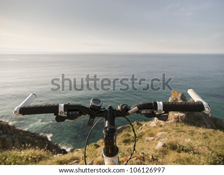 Bicycle handlebars and a coastal landscape. This photo shows the handle in the foreground and background, the sea - stock photo