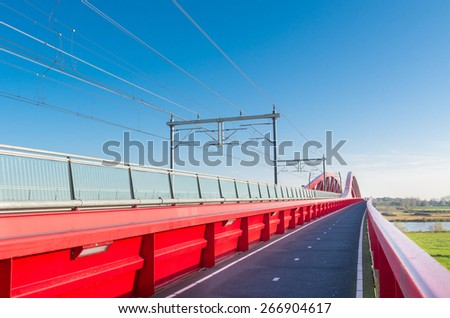 bicycle lane along the new red railroad bridge over the IJssel river in the Netherlands - stock photo