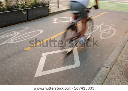 Bicycle Lane, Downtown Vancouver. A cyclist approaching an intersection using a designated bicycle lane which is separated from vehicle traffic in downtown Vancouver, British Columbia, Canada. - stock photo