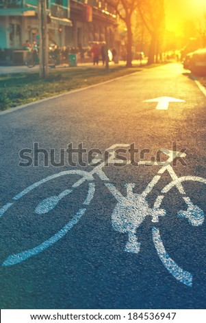 Bicycle lane mark on the street in sunset - stock photo