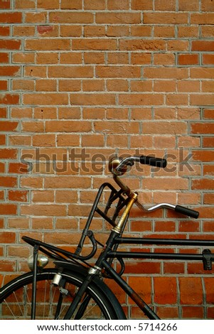 bicycle leaning against brick wall - stock photo