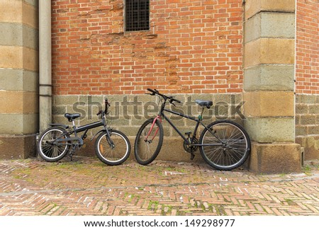 Bicycle leans on the ancient wall of red bricks - stock photo