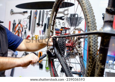 Bicycle mechanic in a workshop in the repair process - stock photo