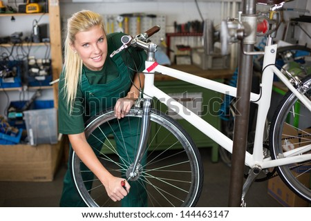 Bicycle mechanic repairing tyre or wheel on bike in a workshop - stock photo