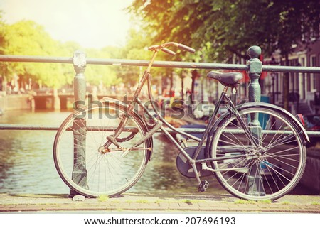 Bicycle on a bridge in sunlight, Amsterdam - stock photo