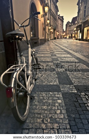 Bicycle on an empty alley with lanterns in Prague at dawn - stock photo