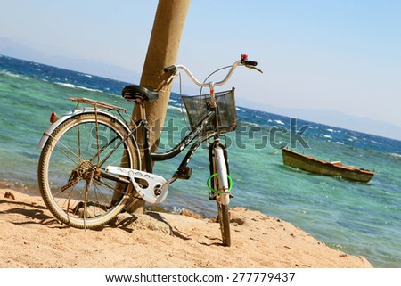 Bicycle on beach against background sea and boat - stock photo