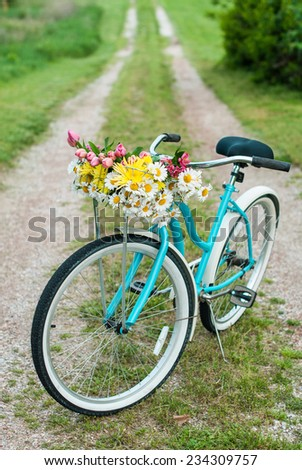 Bicycle on countyside road and a basket of spring flowers with room for copy space. - stock photo