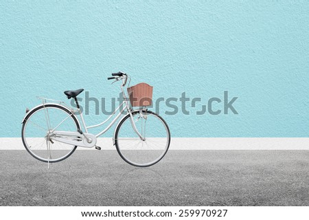 Bicycle on road and blue wall abstract background - stock photo