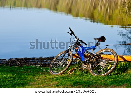 Bicycle on the bank of a forest lake - stock photo