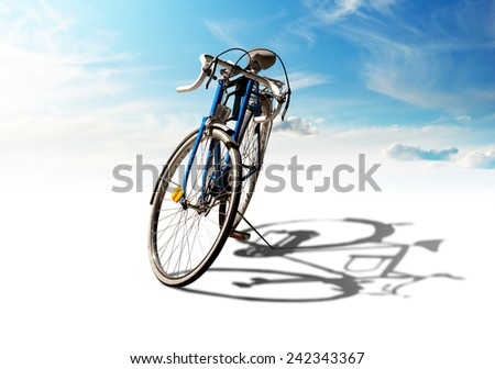 Bicycle parked with shadow on bright day with blue sky - stock photo