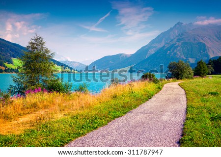 Bicycle path around Resia lake in the Italian Alps. Colorful summer morning on the Reschensee lake. Place is located near the village St. Valentin, Alps, Italy, Europe. - stock photo