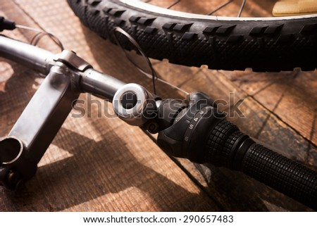 Bicycle repair. Bicycle handle bar and wheel on a wooden work bench. Intentionally shot with low key shadows. Shallow depth of field. Focus is on Shift selector of the handle bar. - stock photo