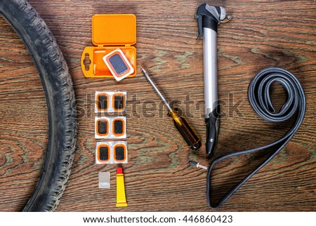 bicycle repair kit, wheels camera on  wooden background - stock photo