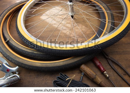 Bicycle repair. Repairing or changing a tire or wheel of an vintage bicycle. Old bicycle wheels on a grungy work desk with well used tools and bicycle parts.   - stock photo
