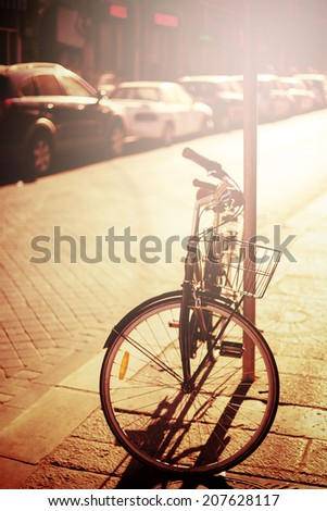 Bicycle resting at the street. Instagram effect, image toned in vintage colors. Selective focus. - stock photo