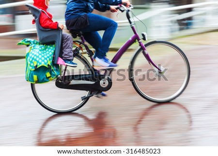 bicycle rider in the rainy city in motion blur - stock photo