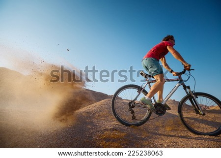 Bicycle rider moving on the desert with lot of dust - stock photo