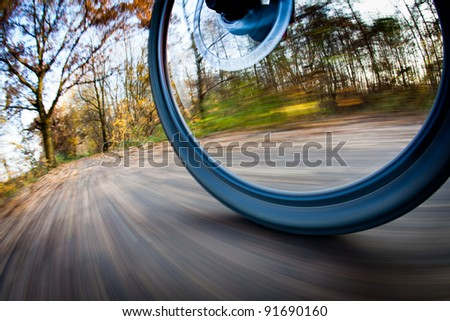 Bicycle riding in a city park on a lovely autumn/fall day (motion blur is used to convey movement) - stock photo