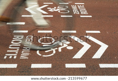 Bicycle riding over a bicycle sign for the city center on a bicycle lane, motion blur of bicycle. - stock photo