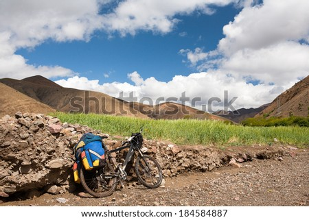bicycle stands leaning on rocks along a winding mountain road in the green fields of wheat and desert mountains behind. Background blue sky with clouds. - stock photo