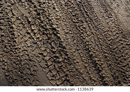 Bicycle tyre tracks in wet brown mud, abstract. - stock photo