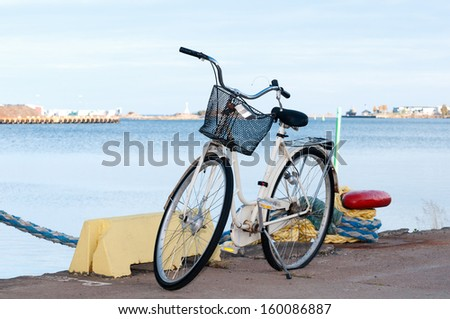 Bicycle with flat tire standing at the pier of Oskarshamn, Sweden, beside a bollard. - stock photo