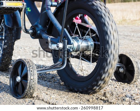 Bicycle with supporting wheels stuck in loose gravel - stock photo