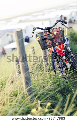 Bicycles leaning aginst fence - stock photo