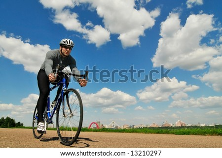 bicyclist on a background of the blue sky - stock photo